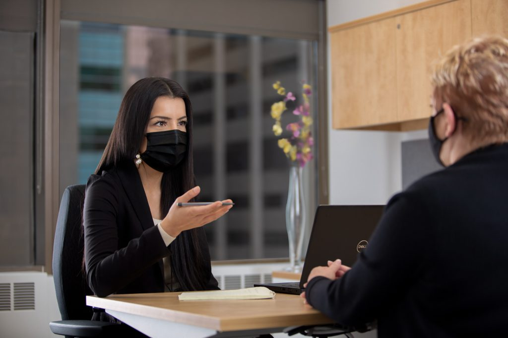 Two women wearing face masks meet in an office.