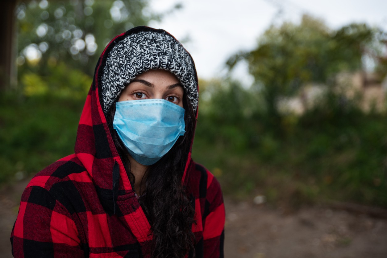 Sad young girl or woman with hood and protective medicine mask standing outside.